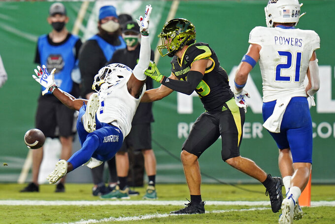 Tulsa safety Kendarin Ray (1) breaks up a pass intended for South Florida wide receiver Bryce Miller (19) during the first half of an NCAA college football game Friday, Oct. 23, 2020, in Tampa, Fla. Defending on the play is safety Bryson Powers (21). (AP Photo/Chris O'Meara)