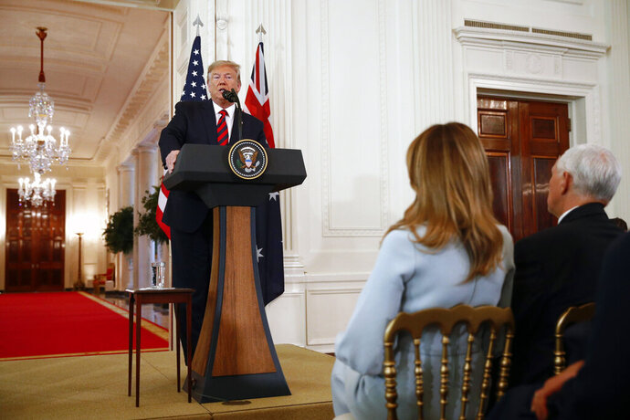 President Donald Trump speaks during a news conference with Australian Prime Minister Scott Morrison in the East Room of the White House, Friday, Sept. 20, 2019, in Washington, as first lady Melania Trump and Vice President Mike Pence listen. (AP Photo/Patrick Semansky)