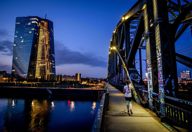 A woman walks over a bridge near the European Central Bank, left, in Frankfurt, Germany, Wednesday, Sept. 30, 2020. (AP Photo/Michael Probst)