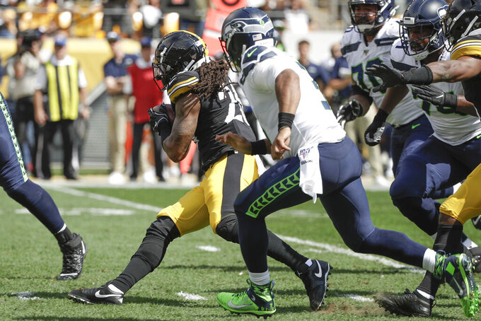 Pittsburgh Steelers inside linebacker Mark Barron (26) runs with the ball past Seattle Seahawks quarterback Russell Wilson (3) after recovering a fumble in the first half of an NFL football game, Sunday, Sept. 15, 2019, in Pittsburgh. (AP Photo/Gene J. Puskar)