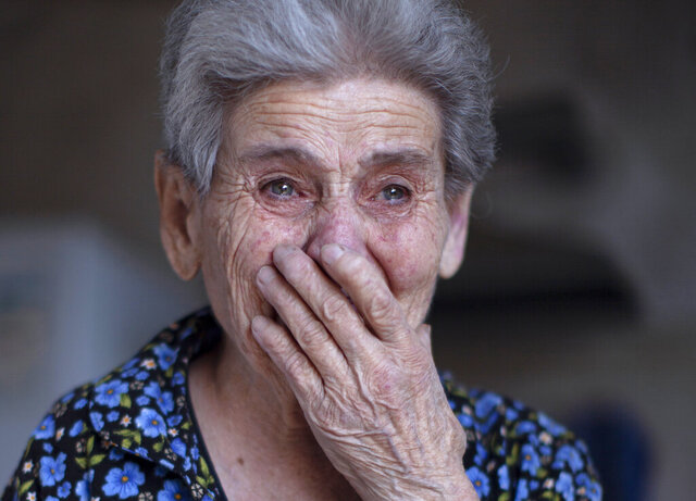 Ethnic Armenian Rosa reacts after her house was damaged during shelling in the town of Martuni, self-proclaimed Republic of Nagorno-Karabakh, Azerbaijan, Tuesday, Sept. 29, 2020. Heavy fighting between Armenian and Azerbaijani forces over the separatist region of Nagorno-Karabakh continued for a fourth straight day on Wednesday, in the biggest escalation of a decades-old conflict in years that has killed dozens and left scores of others wounded. (AP Photo/Karen Mirzoyan)
