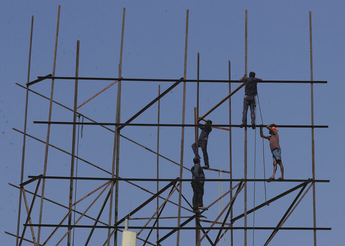 Indian workers repair an advertising hoarding in Hyderabad, India, Tuesday, Jan. 21, 2020. The IMF on Monday lowered India's economic growth estimate for the current fiscal to 4.8% and listed the country's Gross Domestic Product (GDP) numbers as the single biggest drag on its global growth forecast for two years. (AP Photo/Mahesh Kumar A.)
