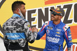 """FILE - Bubba Wallace, left, congratulates Kyle Larson after Larson won a NASCAR Cup Series auto race in Las Vegas, in this Sunday, March 7, 2021, file photo. With few companies willing to back Larson upon his return from a nearly yearlong suspension for using a racial slur, Rick Hendrick put the website for his dealerships on the hood of Larson's car. Larson started winning races, which company officials say drove traffic to HendrickCars.com that netted $1.8 million in leads and over $5 million in television exposure.  """"We're having the best year we've ever had,"""" said Hendrick, owner of the largest privately held dealership in the country. """"The market is blazing.""""(AP Photo/John Locher, File)"""