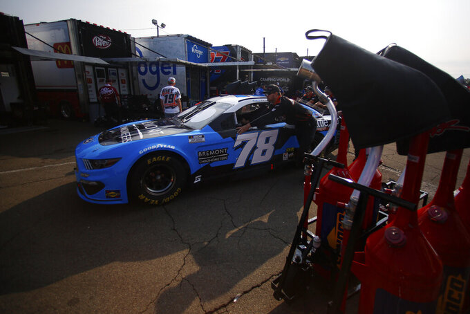 Pit crews push Kyle Tilley's car through the garage area before a NASCAR Cup Series auto race in Watkins Glen, N.Y., on Sunday, Aug. 8, 2021. (AP Photo/Joshua Bessex)