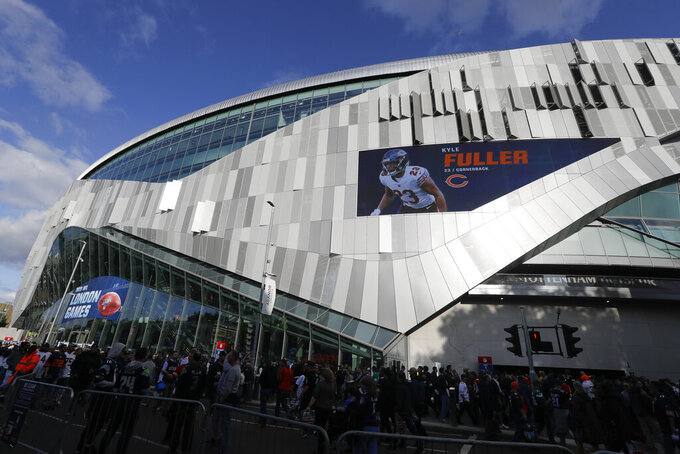 CORRECTS STADIUM TO TOTTENHAM HOTSPUR STADIUM INSTEAD OF WEMBLEY STADIUM  - Fans wait to enter Tottenham Hotspur Stadium before an NFL football game between the Chicago Bears and the Oakland Raiders, Sunday, Oct. 6, 2019, in London. (AP Photo/Kirsty Wigglesworth)