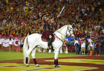 Hector Aguilar rides Traveler VII during the second half of an NCAA college football game between Southern California and Utah, Saturday, Oct. 24, 2015, in Los Angeles. Football is being played in the Power Five conferences, but many of the longstanding traditions that go along with the games are on hold during the coronavirus pandemic. (AP Photo/Mark J. Terrill)