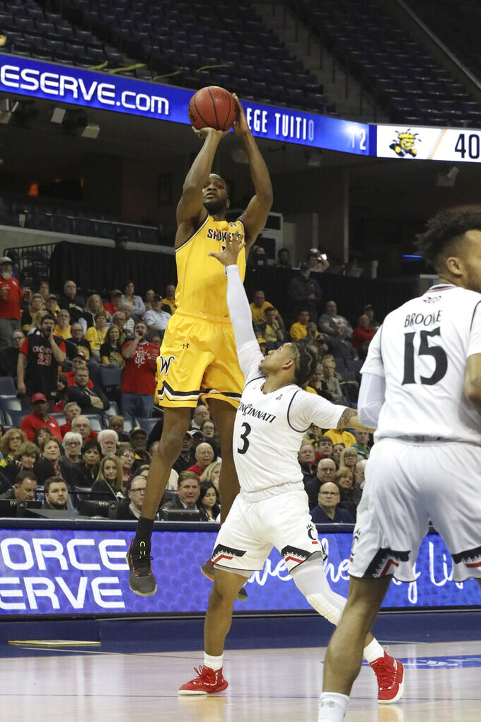 Wichita State's Dexter Daniels shoots for three over Cincinnati player Justin Jenifer in the second half of an NCAA college basketball game at the American Athletic Conference tournament Saturday, March 16, 2019, in Memphis, Tenn. (AP Photo/Troy Glasgow)