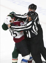 Two officials try to break up a fight between Colorado Avalanche's Logan O