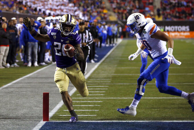 Washington running back Salvon Ahmed, left, makes it into the end zone ahead of Boise State safety Kekoa Nawahine for Washington's second touchdown during the first half of the Las Vegas Bowl NCAA college football game at Sam Boyd Stadium, Saturday, Dec. 21, 2019, in Las Vegas. (AP Photo/Steve Marcus)