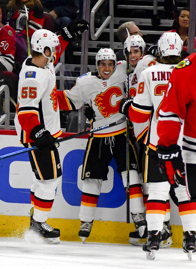 Calgary Flames left wing Johnny Gaudreau, second from left, celebrates with teammates after scoring a goal past Chicago Blackhawks goaltender Collin Delia during the first period of an NHL hockey game on Monday Jan. 7, 2019, in Chicago. (AP Photo/Matt Marton)