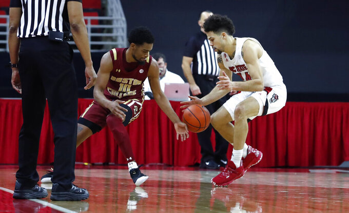 North Carolina State's Devon Daniels (24) knocks the ball from Boston College's Wynston Tabbs (10) in the final minute of an NCAA college basketball game in Raleigh, N.C., Wednesday, Dec. 30, 2020. (Ethan Hyman/The News & Observer via AP, Pool)