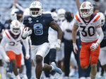 North Carolina's Michael Carter (8) breaks away from Virginia Tech's Tyler Matheny (30) for a 62-yard touchdown in the fourth quarter of an NCAA college football game, Saturday, Oct. 10, 2020 at Kenan Stadium in Chapel Hill, N.C. (Robert Willett/The News & Observer via AP)