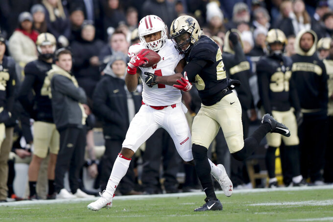 Wisconsin wide receiver A.J. Taylor (4) makes a catch as he's hit by Purdue safety Navon Mosley Purdue cornerback Simeon Smiley (29) during the first half of an NCAA college football game in West Lafayette, Ind., Saturday, Nov. 17, 2018. (AP Photo/Michael Conroy)