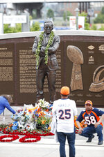 Fans gather for photographs at the foot of a statue during a five-hour memorial for Denver Broncos owner Pat Bowlen Tuesday, June 18, 2019 in at Mile High Stadium, the NFL football team's home in Denver. Bowlen, who has owned the franchise for more than three decades, died last Thursday. (AP Photo/David Zalubowski)