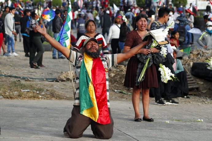 A coca leaf producer kneels holding a bible with his arms outspread asking police to open the way so a march by backers of former President Evo Morales may continue to Cochabamba, Bolivia, Saturday, Nov. 16, 2019. Officials now say at least eight people died when Bolivian security forces fired on Morales supporters the day before, in Sacaba. The U.N. human rights chief says she's worried that Bolivia could