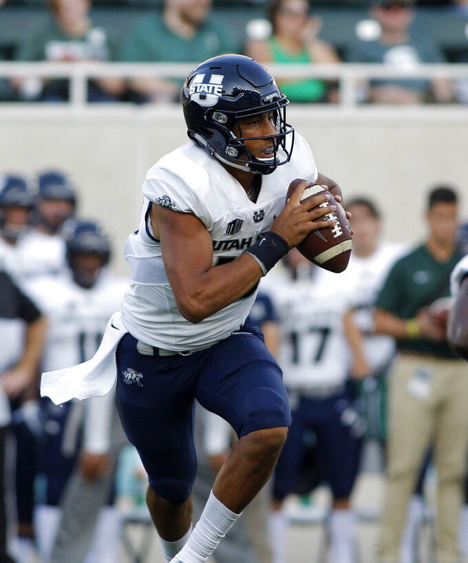 Utah State quarterback Jordan Love rolls out against Michigan State during the first quarter of an NCAA college football game, Friday, Aug. 31, 2018, in East Lansing, Mich. (AP Photo/Al Goldis)