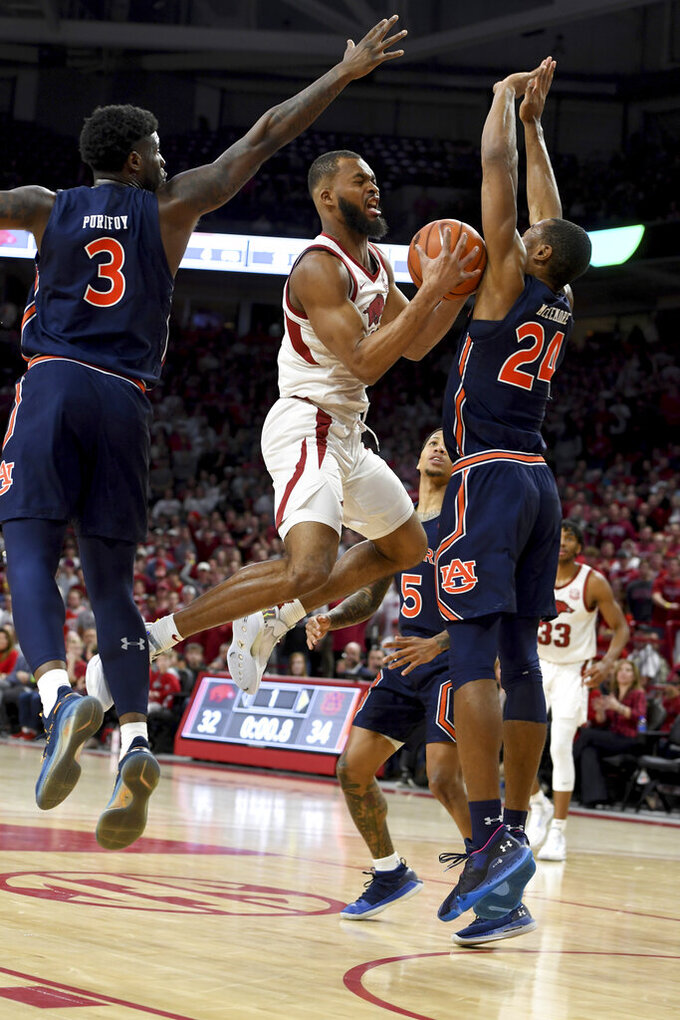 Arkansas forward Jeantal Cylla (0) tries to drive past Auburn defenders Danjel Purifoy (3) and Anfernee McLemore (24) during the first half of an NCAA college basketball game Tuesday, Feb. 4, 2020, in Fayetteville, Ark. (AP Photo/Michael Woods)