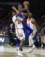 Kansas' Marcus Garrett (0) shoots between Oklahoma's Jamal Bieniemy (24) and Kristian Doolittle (21) during the first half of an NCAA college basketball game in Norman, Okla., Tuesday, Jan. 14, 2020. (AP Photo/Garett Fisbeck)