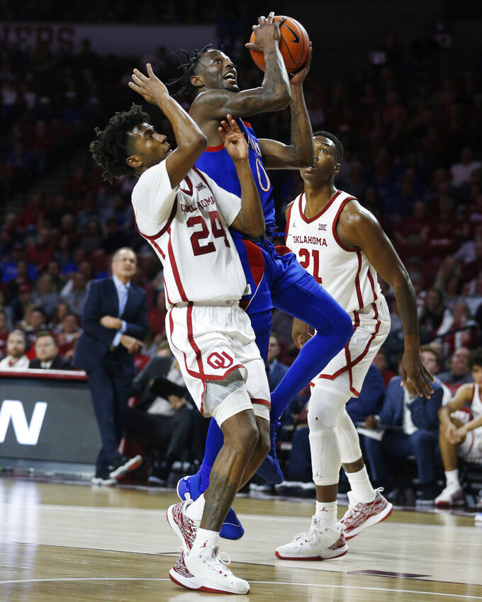 Kansas' Marcus Garrett (0) shoots between Oklahoma's Jamal Bieniemy (24) and Kristian Doolittle (21) during the first half of an NCAA college basketball game in Norman, Okla., Tuesday, Jan. 14, 2020. (AP Photo/Garett Fisbeck)