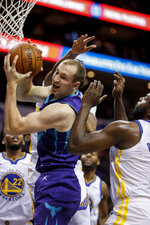 Charlotte Hornets forward Cody Zeller pulls down an offensive rebound during the first half of the team's NBA basketball game against the Golden State Warriors in Charlotte, N.C., Wednesday, Dec. 4, 2019. (AP Photo/Nell Redmond)