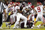 Texas A&M running back Isaiah Spiller (28) is meet at the line of scrimmage by the Arkansas defense for a loss during the first quarter of an NCAA college football game Saturday, Oct. 31, 2020, in College Station, Texas. (AP Photo/Sam Craft)