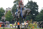 Crews remove one of the country's largest remaining monuments to the Confederacy, a towering statue of Confederate General Robert E. Lee on Monument Avenue in Richmond, Va., Wednesday, Sept. 8, 2021. (AP Photo/Steve Helber)