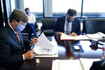 Mississippi Gov. Tate Reeves, left, reviews a sample ballot while Secretary of State Michael Watson, right, reads the names of those persons who have qualified to run for president on the fall election ballot during a meeting of the State Board of Election Commissioners, Tuesday, Sept. 8, 2020, in Jackson, Miss. Kanye West will appear as a presidential candidate on Mississippi's ballot in November, after being approved as a qualified candidate by the State Board of Election Commissioners on Tuesday.(AP Photo/Rogelio V. Solis)