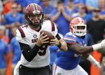 South Carolina quarterback Jake Bentley, left, scrambles as he is pressured by the Florida defense during the first half of an NCAA college football game, Saturday, Nov. 10, 2018, in Gainesville, Fla. (AP Photo/John Raoux)