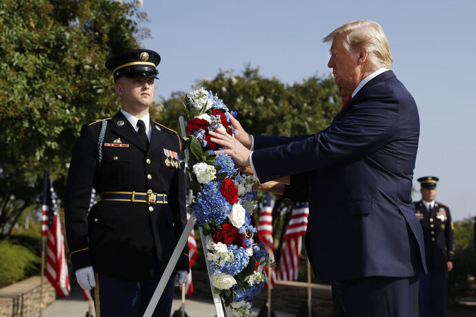 President Donald Trump and first lady Melania Trump place a wreath  and will participate in a moment of silence honoring the victims of the Sept. 11 terrorist attacks, Wednesday, Sept. 11, 2019, at the Pentagon. (AP Photo/Evan Vucci)