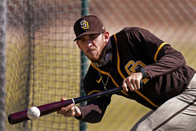 San Diego Padres' Joe Musgrove bunts during spring training baseball practice Tuesday, Feb. 23, 2021, in Peoria, Ariz. (AP Photo/Charlie Riedel)