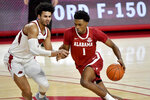 Alabama forward Herbert Jones (1) tries to get past Arkansas forward Justin Smith during the second half of an NCAA college basketball game in Fayetteville, Ark., Wednesday, Feb. 24, 2021. (AP Photo/Michael Woods)