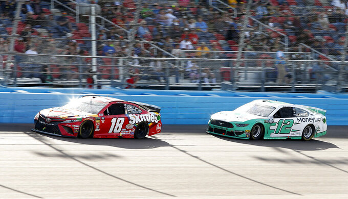 Kyle Busch (18) leads Ryan Blaney (12) through Turn 4 during the NASCAR Cup Series auto race at ISM Raceway, Sunday, March 10, 2019, in Avondale, Ariz. (AP Photo/Ralph Freso)