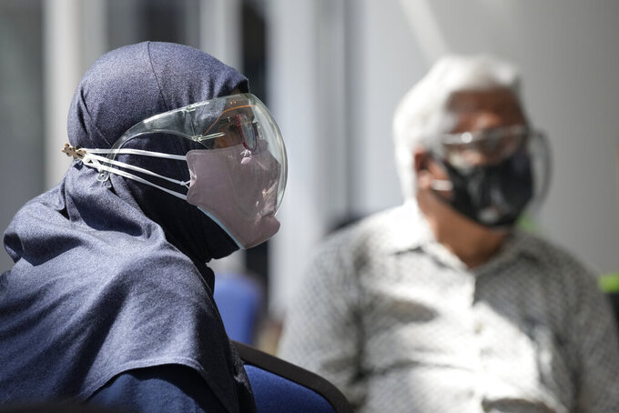 A Muslim couple wearing face mask and face shield while waiting for vaccine for the coronavirus disease (COVID-19) at a vaccination centre in Kuala Lumpur, Malaysia, Monday, May 31, 2021. An exhibition center in Malaysia has been turned into the country's first mega vaccination center as the government aims to speed up inoculations amid a sharp spike in infections. (AP Photo/Vincent Thian)