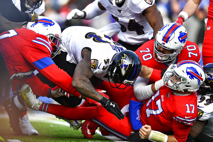 Buffalo Bills quarterback Josh Allen (17) has the ball knocked loose as he is hit by Baltimore Ravens outside linebacker Matt Judon (99), right, during the first half of an NFL football game in Orchard Park, N.Y., Sunday, Dec. 8, 2019. The fumble was recovered by Ravens defensive end Jihad Ward (53). (AP Photo/Adrian Kraus)