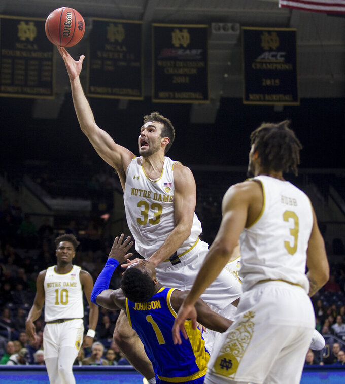 Notre Dame's John Mooney (33) gets called for a charging violation as he goes up for a shot over Pittsburgh's Xavier Johnson (1) during the first half of an NCAA college basketball game Wednesday, Feb. 5, 2020, in South Bend, Ind. (AP Photo/Robert Franklin)