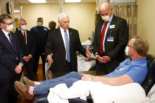 Vice President Mike Pence, center, visits Dennis Nelson, a patient who survived the coronavirus and was going to give blood, during a tour of the Mayo Clinic Tuesday, April 28, 2020, in Rochester, Minn., as he toured the facilities supporting COVID-19 research and treatment. Pence chose not to wear a face mask while touring the Mayo Clinic in Minnesota. It's an apparent violation of the world-renowned medical center's policy requiring them. (AP Photo/Jim Mone)