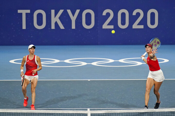 The Swiss doubles team of Viktorija Golubic, left, and Belinda Bencic, of Switzerland, play an Australian doubles team during the quarterfinal round of the tennis competition at the 2020 Summer Olympics, Wednesday, July 28, 2021, in Tokyo, Japan. (AP Photo/Seth Wenig)