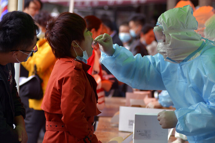 A medical staff takes a swab from a woman as residents line up for the COVID-19 test near the residential area in Qingdao in east China's Shandong province on Monday, Oct. 12, 2020. Authorities in the eastern Chinese port city of Qingdao said Tuesday that they have completed coronavirus tests on more than 3 million people following the country's first reported local outbreak of the virus in nearly two months. (Chinatopix ia AP)