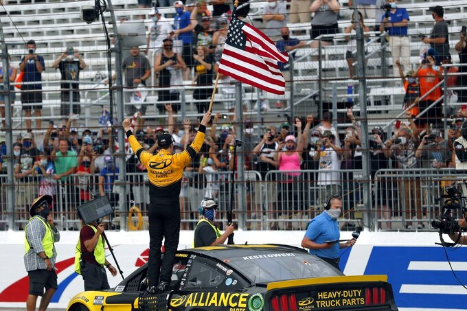 Driver Brad Keselowski celebrates with the American flag after winning during a NASCAR Cup Series auto race, Sunday, Aug. 2, 2020, at the New Hampshire Motor Speedway in Loudon, N.H. (AP Photo/Charles Krupa)