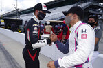 Rinus VeeKay, left, of the Netherlands, and Alex Palou, of Spain, shake hands after they qualified for the Indianapolis 500 auto race at Indianapolis Motor Speedway, Sunday, Aug. 16, 2020, in Indianapolis. (AP Photo/Darron Cummings)