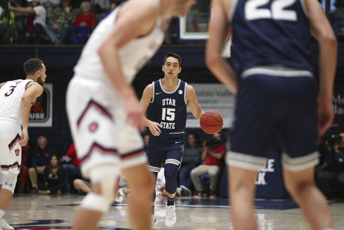 Utah State guard Abel Porter (15) brings the ball up during the first half of the team's NCAA college basketball game against Saint Mary's in Moraga, Calif., Friday, Nov. 29, 2019. (AP Photo/Jed Jacobsohn)