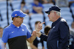 Duke head coach David Cutcliffe, left, and North Carolina head coach Mack Brown speak prior to an NCAA college football game in Chapel Hill, N.C., Saturday, Oct. 26, 2019. (AP Photo/Gerry Broome)