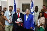 Israel's Prime Minister Benjamin Netanyahu, center left, and the New England Patriots owner Robert Kraft, venter right, pose for a photo in Jerusalem, Thursday, June 20, 2019. Israel will honor Kraft with the 2019 Genesis Prize for his philanthropy and commitment to combatting anti-Semitism. (AP Photo/Sebastian Scheiner)