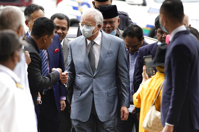 Former Malaysian Prime Minister Najib Razak, center, wearing a face mask greets his supporters upon arrival at court house in Kuala Lumpur, Malaysia, Thursday, June 4, 2020. Closing arguments are expected in the first corruption trial of him linked to the multibillion-dollar looting of the 1MDB state investment fund. (AP Photo/Vincent Thian)