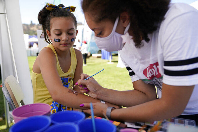 Francesca Dehorta, 9, left, has a bear painted on her arm by Ayla Rose Barreau while tailgating before an NCAA college football game between the Hawaii Warriors and the UCLA Bruins Saturday, Aug. 28, 2021, in Pasadena, Calif. Colleges across the country are cautiously optimistic that pregame tailgating will largely return to normal even since the emergence of the delta variant of the coronavirus. (AP Photo/Ashley Landis)