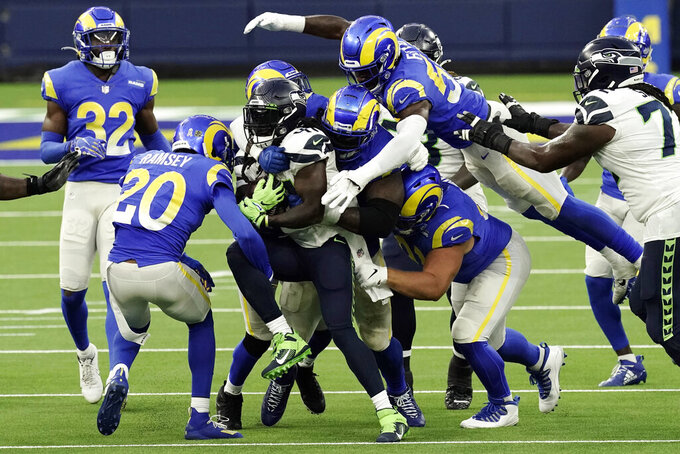 Seattle Seahawks running back Alex Collins, center, is tackled by a group of Los Angeles Rams defenders during the second half of an NFL football game Sunday, Nov. 15, 2020, in Inglewood, Calif. (AP Photo/Jae C. Hong)