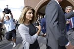 FILE - In this Aug. 27, 2019, file photo, actress Lori Loughlin departs federal court in Boston, after a hearing in a nationwide college admissions bribery scandal. Loughlin and her fashion designer husband Mossimo Giannulli are fighting expanded charges against them in the college admissions bribery scandal. Lawyers for the couple entered not guilty pleas on their behalf Tuesday, Nov. 19, 2019, to charges of conspiracy to commit federal program bribery. (AP Photo/Steven Senne, File)
