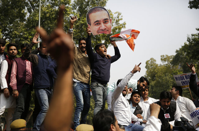 FILE- In this Feb. 16, 2018 file photo, activists of India's opposition Congress party's youth wing shout slogans against the ruling Bharatiya Janata Party (BJP) as one of them holds a severed head from a cut out photograph of billionaire jeweler Nirav Modi in New Delhi, India. Indian authorities say they have brought from Hong Kong polished diamonds and pearls worth millions of dollars belonging to India's fugitive diamond merchant Nirav Modi who is fighting a court battle in London for his extradition to New Delhi.  (AP Photo/Altaf Qadri, File)