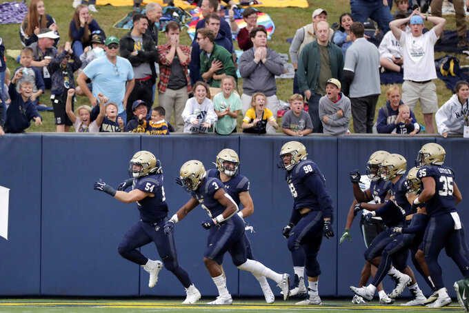 Navy linebacker Diego Fagot, far left, celebrates after returning an interception off a pass from Tulane quarterback Justin McMillan, not visible, for a touchdown during the first half of an NCAA college football game, Saturday, Oct. 26, 2019, in Annapolis. (AP Photo/Julio Cortez)