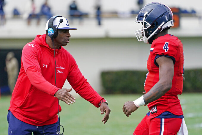 Jackson State football coach Deion Sanders, left, congratulates quarterback Jalon Jones (4) after guiding the team to a touchdown against Edward Waters during the first half of an NCAA college football in Jackson, Miss., Sunday, Feb. 21, 2021. The game marked the head coaching debut of Sanders. (AP Photo/Rogelio V. Solis)